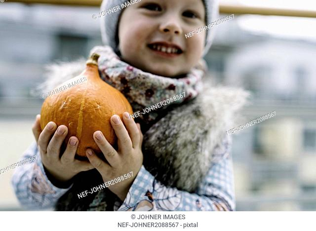 Boy holding pumpkin outdoors