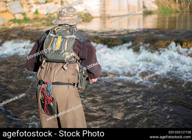Young man flyfishing on the river