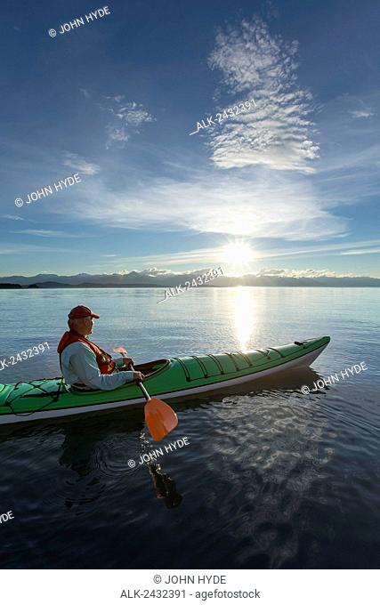 Evening sea kayaking in Lynn Canal near Eagle Beach State Recreation Area, Juneau, Alaska, Chilkat Mountains beyond in the distance