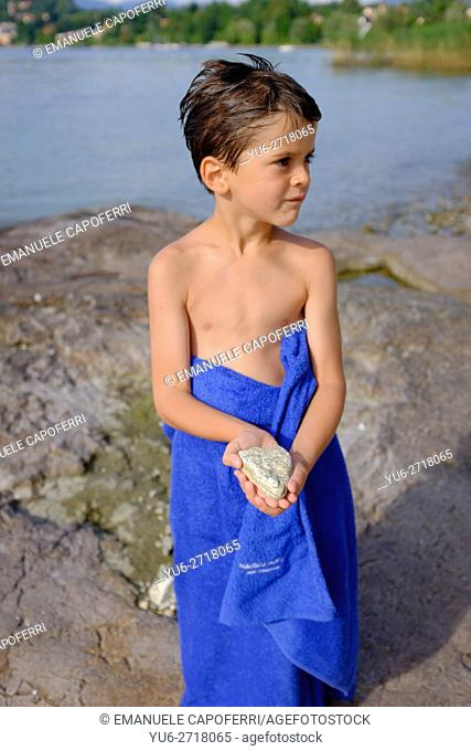 Portrait of a 7 year old with a towel around his waist, at the beach on Lake Maggiore, Italy