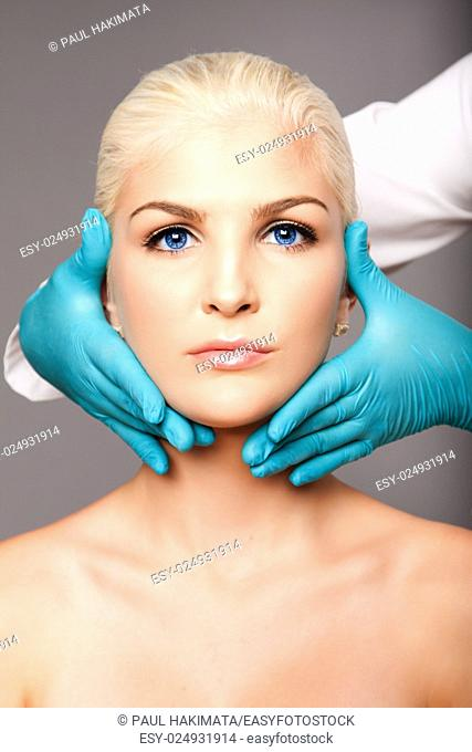 Beautiful face of young woman for Aesthetics facial skincare concept touched by cosmetic plastic surgeon beautician