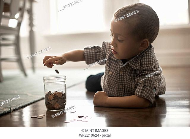 A child lying on his stomach on the floor playing with coins and putting them in a glass jar