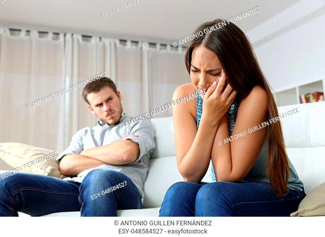 Woman lamenting domestic violence beside her angry husband sitting on a couch in the living room in a house indoor