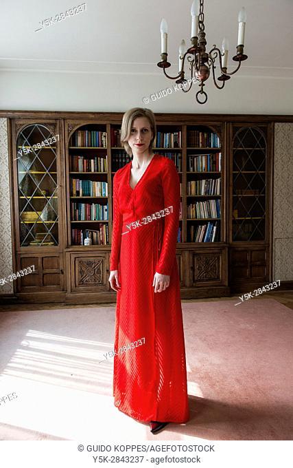 Tilburg, Netherlands. Woman in Red Dress inside her vintage reading room library