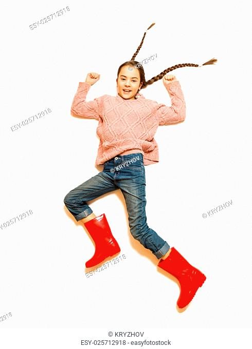 Isolated shot of cute smiling girl in red rubber boots jumping high