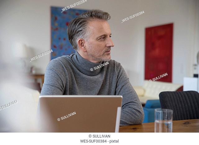 Businessman working on computer in apartment
