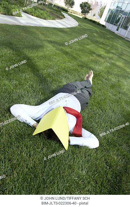 Businessman lying in the grass with a file folder over his face, Redwood City, California, United States