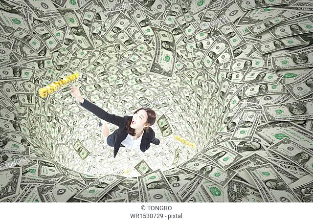 a business woman falling into a hole full of money