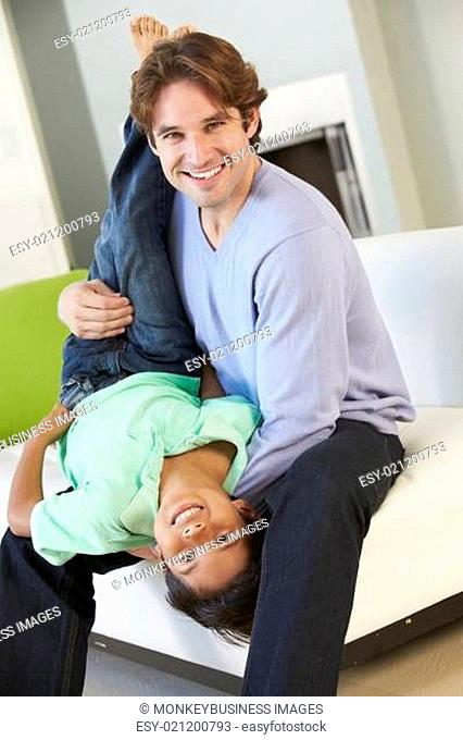 Father And Son Having Fun On Sofa Together