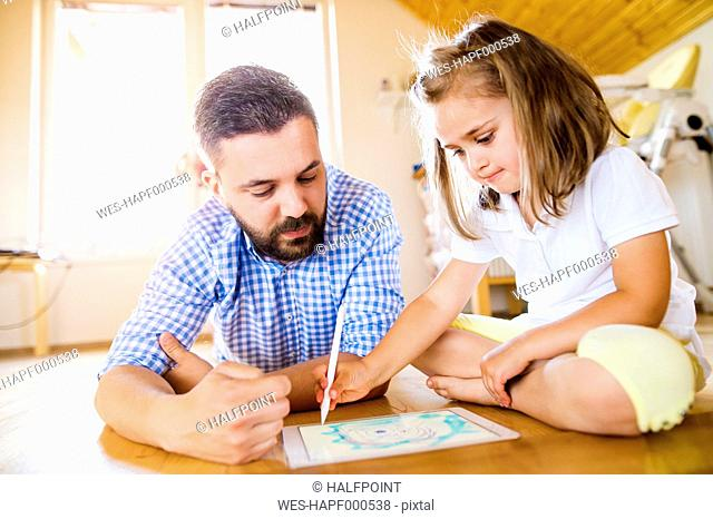 Father and daughter lying on floor, drawing on digital tablet