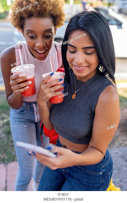 USA, Florida, Miami Beach, two happy female friends with cell phone and soft drink in the city