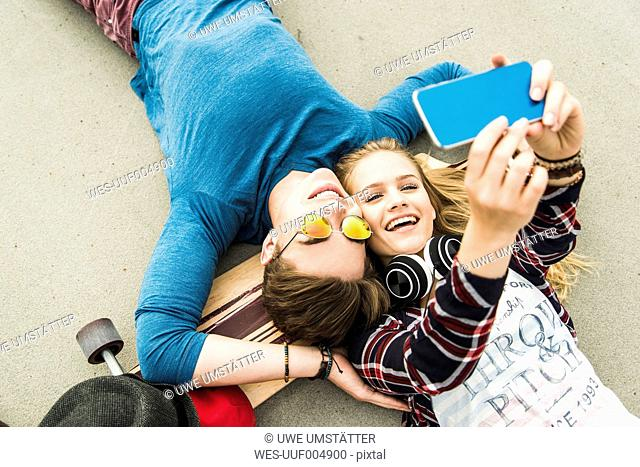 Happy young couple lying on ground with skateboard looking at cell phone