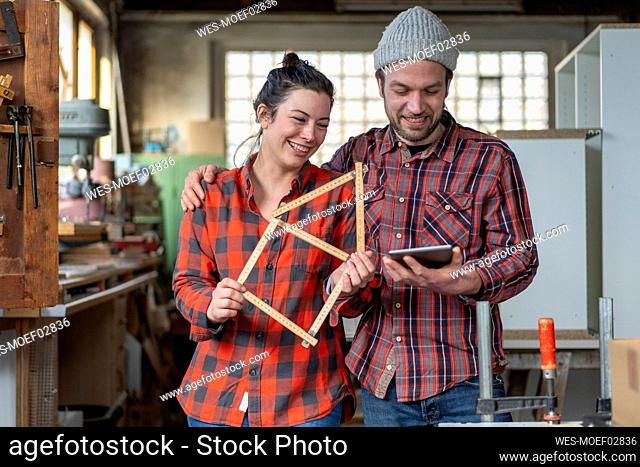 Portrait of happy craftswoman and craftsman holding tablet and yardstick in their workshop