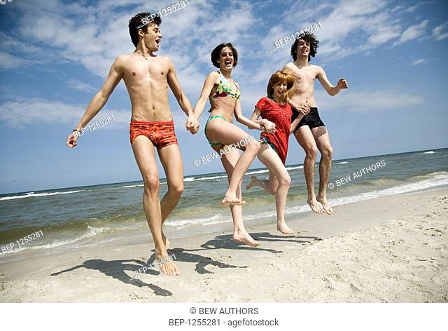 Group of friends jumping on the beach holding each others hands
