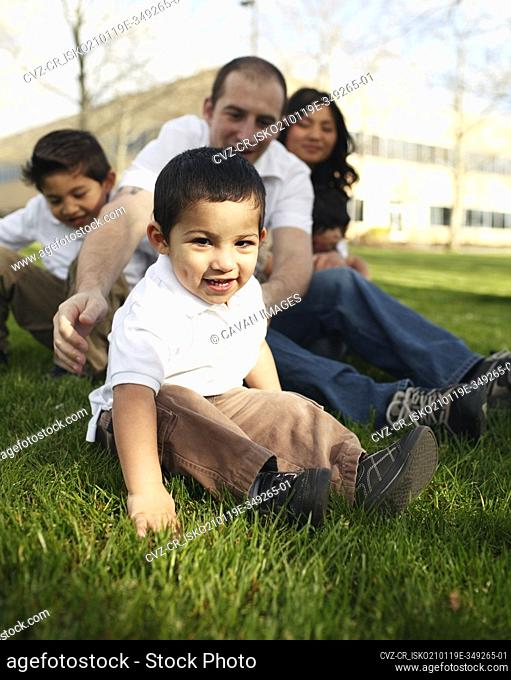Familiy sitting in the grass in park