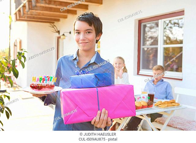 Portrait of teenage boy carrying birthday cake and birthday gifts on patio