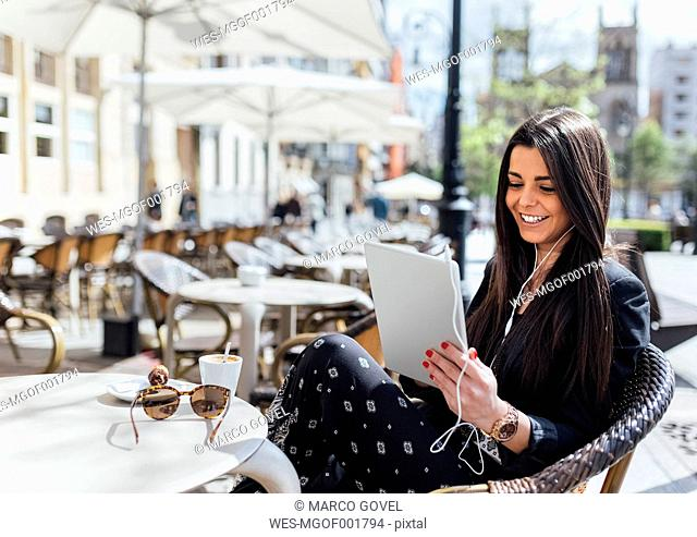 Pretty young woman having coffee, digital tablet, listening music, pavement cafe