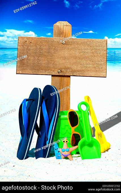 Strandspielzeug, Flip Flops und großes Holzschild