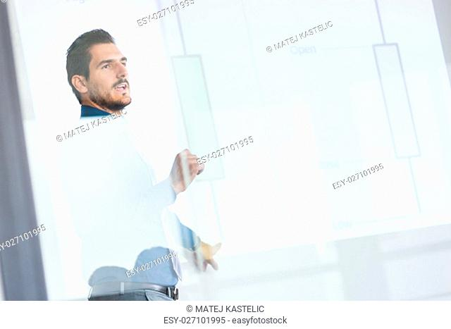 Business man making a presentation in front of whiteboard. Business executive delivering a presentation to his colleagues during meeting or in-house business...