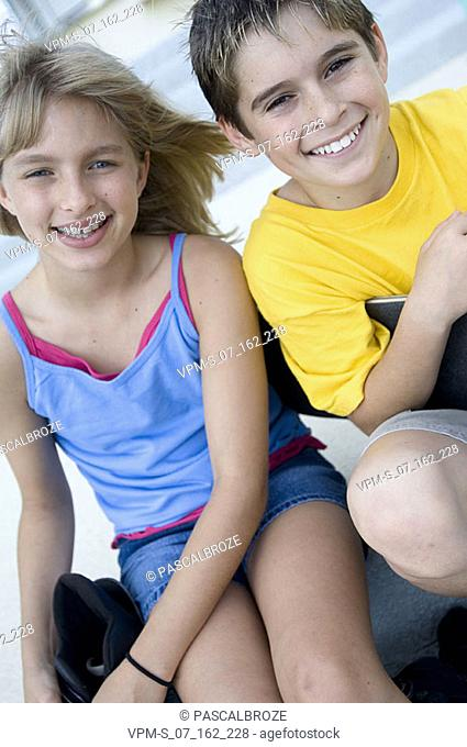 Portrait of a boy and his sister sitting together and smiling