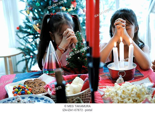 Two sisters praying with their hands clasped at Christmas