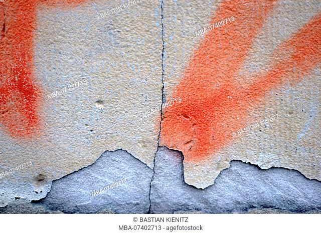 Close-up of a wall with a chipped and painted plaster layer