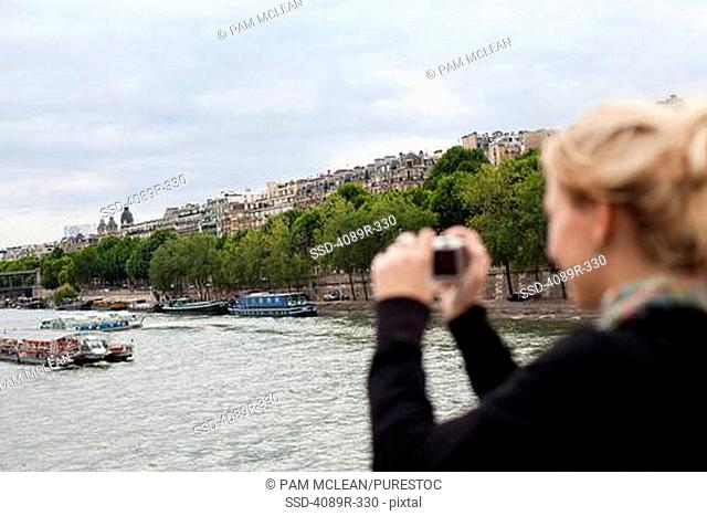 France, Ile-De-France, Paris, Teenage girl photographing Seine River