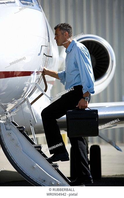 Profile of a businessman entering an airplane