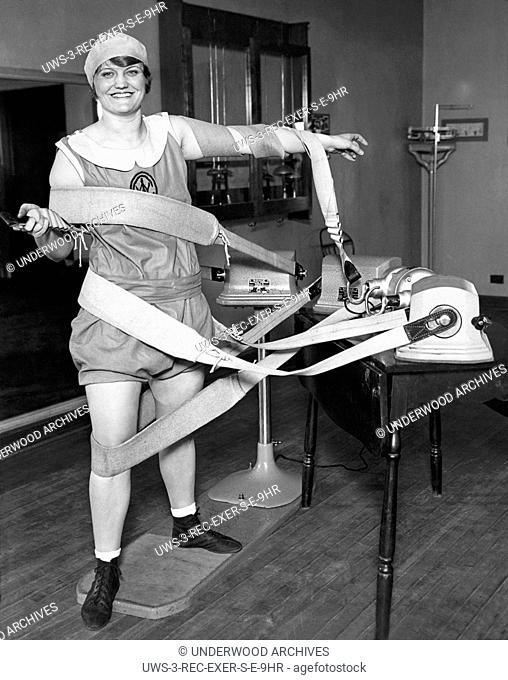 Chicago, Illinois: May 9, 1929.A woman is tangled up in the straps from the tummy shimmy machines at her athletic club