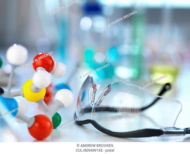 Safety glasses and molecular model on laboratory bench