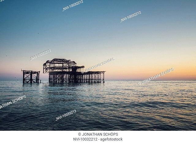 Burnt West Pier at dusk, Brighton, England