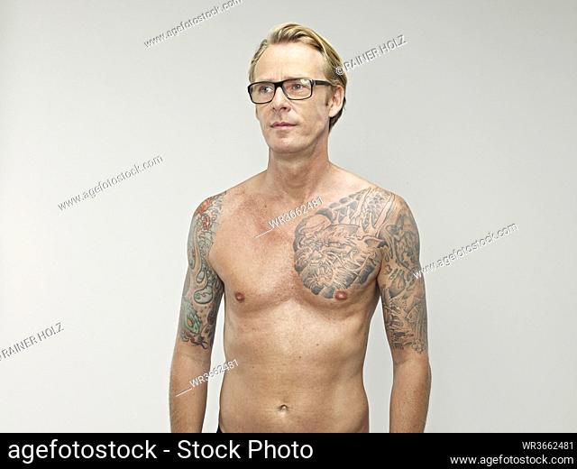 Mature man looking away with tatoos