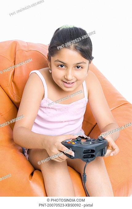 Portrait of a girl sitting on a bean bag and playing a video game