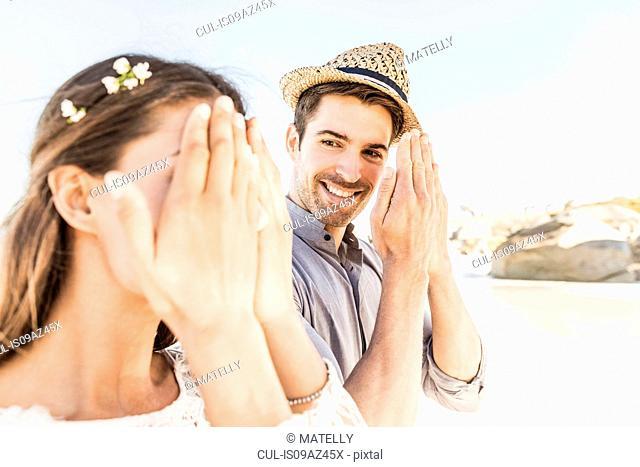 Man peeking at girlfriend hiding face on beach, Cape Town, South Africa