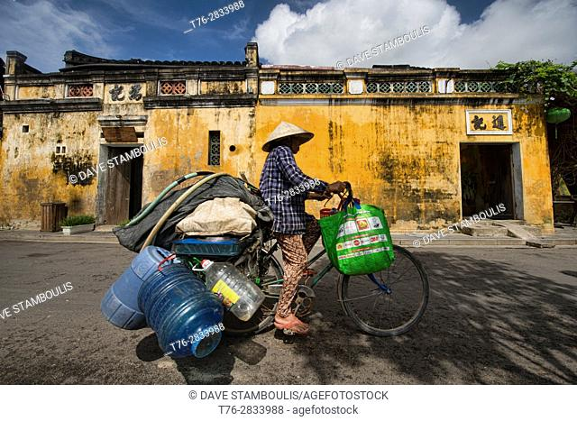 Bicycling with a load in the picturesque old town of Hoi An, Vietnam