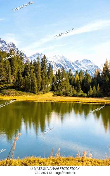Alpine lake with trees and snow-capped mountain in Grisons, Switzerland