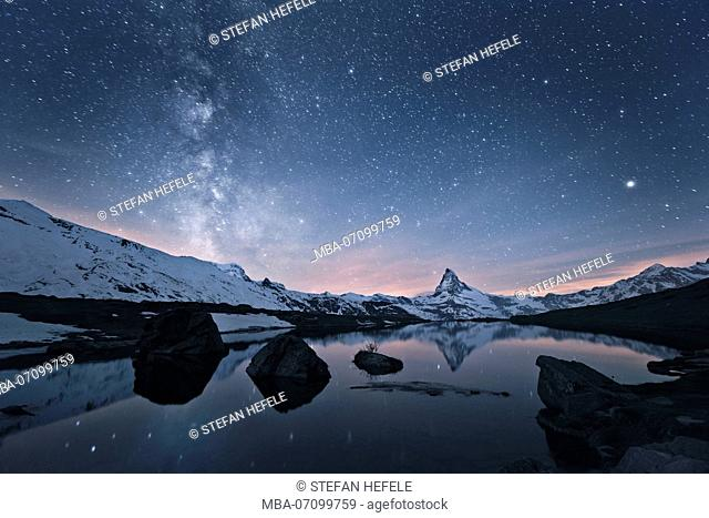 Milky way over the Matterhorn (mountain) with reflection in Stellisee (lake), Switzerland