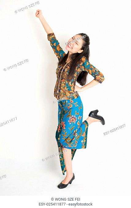 Full length portrait of Southeast Asian female in batik dress arms up, cheering and jumping around on plain background