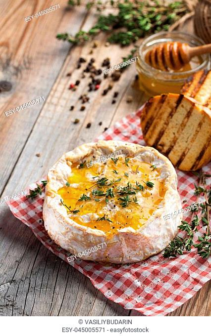 A real Camembert from France with thyme, honey and toasted bread on old wooden rustic table. Soft cheese on a wooden background. Top view