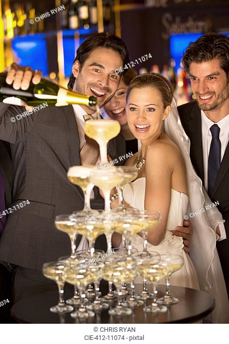 Groom pouring champagne pyramid at wedding reception
