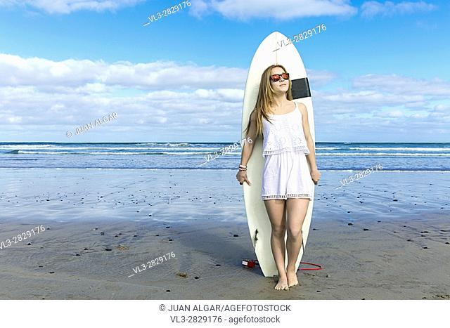 Female wearing sunglasses standing at the beach with surfboard. Horizontal outdoors shot