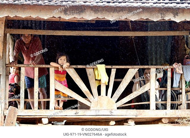 Jarai (Gia Rai) ethnic group. A family inside their traditional home during the monsoon. Kon Tum. Vietnam