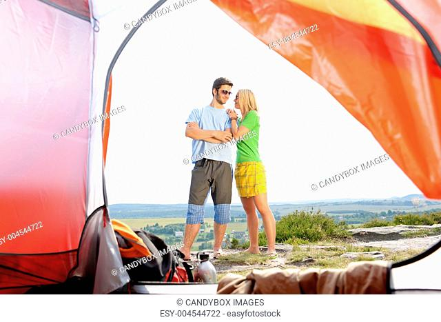 Camping young couple outside tent panoramic view
