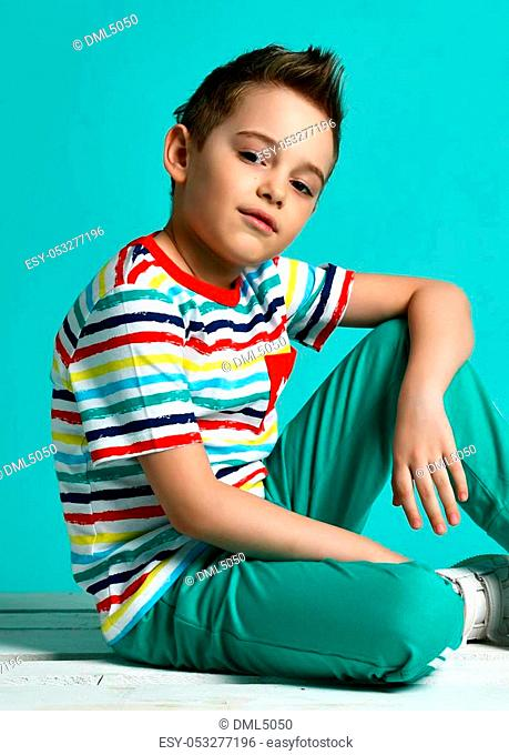 Happy young boy sittingin stripes casual shirt positive attitude on blue mint background