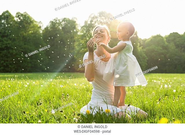 Mother and daughter with blowball on meadow in summer