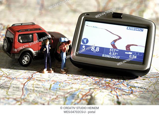 Navigation instrument, figurines and motorcar on a map