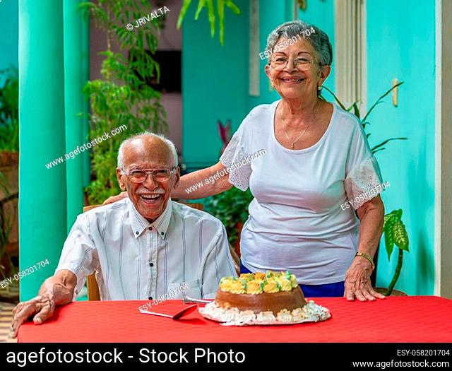 Smiling elderly couple sitting in front of a cake