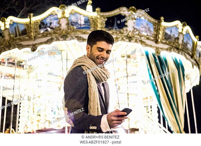 Man using his cell phone at a carousel at night