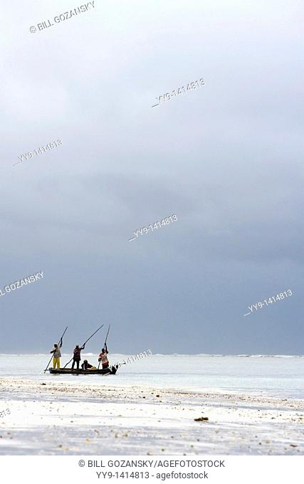 Fisherman poling wooden boat near shoreline - Diani Beach - near Mombasa, Kenya