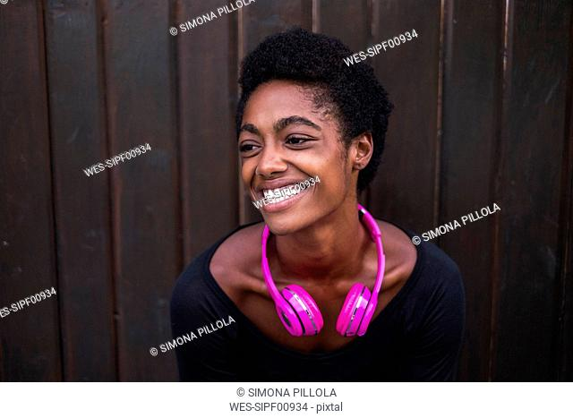 Portrait of laughing woman with pink headphones